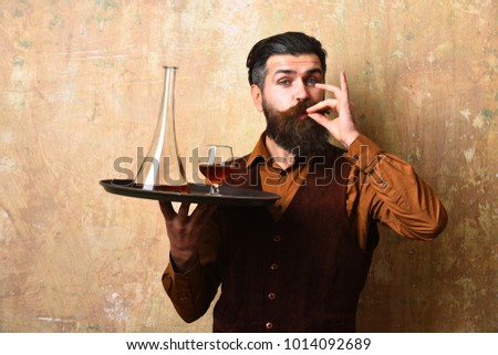 Barman with satisfied face serves scotch. Waiter with glass and bottle of whiskey on tray. Man with beard shows perfection sign holding cognac on beige wall background. Service and catering concept