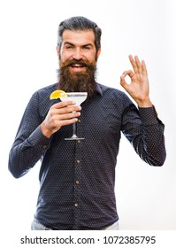 Barman serving cocktail margarita. Man with beard on happy smiling face shows ok gesture on white background.