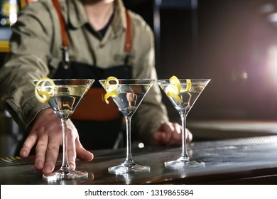 Barman serving glasses of lemon drop martini on counter, closeup. Space for text
