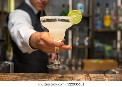 Barman serving margarita cocktail