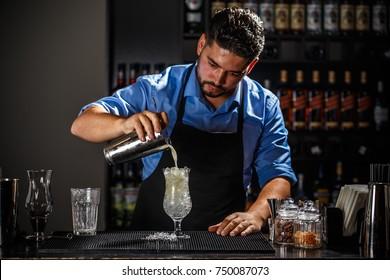 Barman with shaker preparing pina colada cocktail at bar