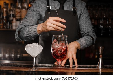 Barman in shirt and apron stirring an alcoholic drink with ice in a cocktail glass