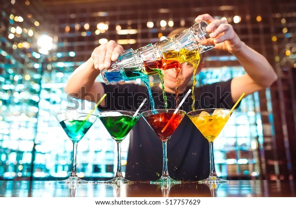 Barman show. Bartender pours alcoholic cocktails.