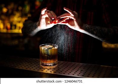 Barman splashing orange peel juice into a strong cocktail in the dark background of bar