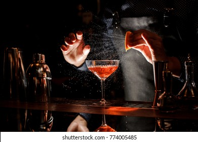 Barman sprinkling the orange juice into the cocktail on the dark background of bar counter