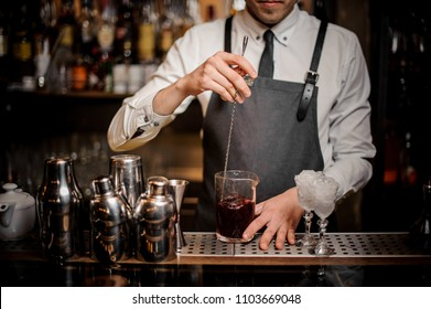 Barman stirring a fresh and tasty summer alcoholic cocktail in glass on the bar counter