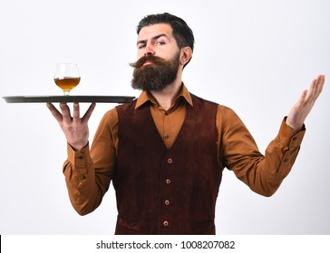 Barman with strict face serves cognac. Luxury beverage concept. Man with beard holds glass with alcohol on white background. Waiter in vintage vest with whiskey or scotch on tray.