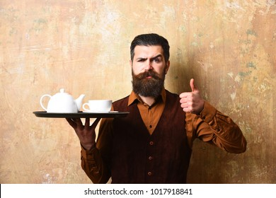Barman with strict face serves tea or coffee showing thumbs up. Man with beard and mustache holds tea on beige wall background. Waiter with white tea cup and pot on tray. Service and catering concept