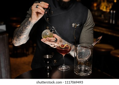 Barman with tattoo making a fresh and sweet summer cocktail with cherries and syrup using professional bar utensils on the counter