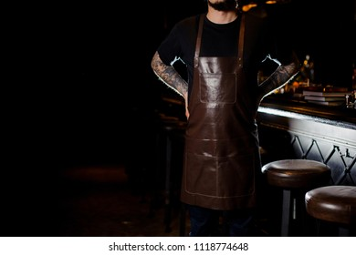 Barman with tattoo on hand dressed in dark brown leather apron standing near the dark bar counter in night club