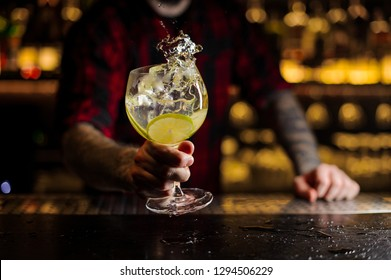 Barman with tattoos holding a cocktail glass with fresh sour and sweet citrus drink with slices of lime