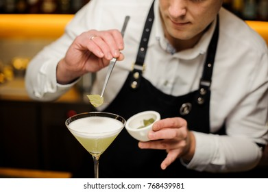 Barman in a white shirt and apron decorating a cocktail glass with a tiny birch leaf