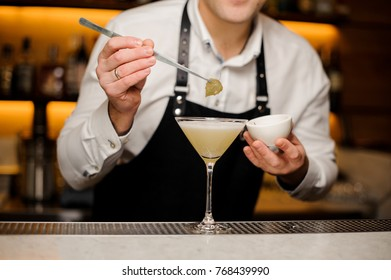 Barman in white shirt and apron decorating a cocktail glass with a tiny birch leaf