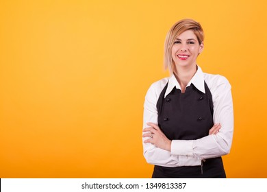 Barman woman looking at the camera and smiling over yellow background. Skilled coffeemaker. . Attractive woman.