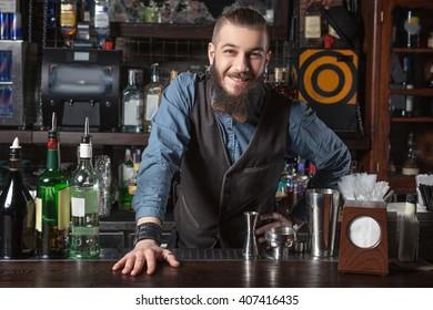 Barman at work looking at camera.