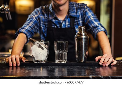 Barman at work pouring hard spirit into glasses and preparing cocktails in detail