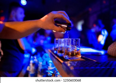 barman at work, pouring spirit into a glass. concept about professions and drinks