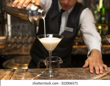 Barman at work, preparing cocktails. pouring pina colada to cocktail glass. concept about service and beverages.