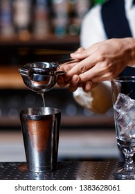 barman at work. A young bartender works with a shaker.