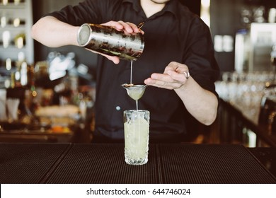 Barman's hands in bar interior making non-alcohol cocktail. Professional bartender at work mixing ice in glass for drink. Party time in night club
