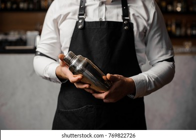 Barman`s hands holding a professional shaker against the blurred indoors background of the bar counter