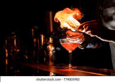Barman`s hands making a fresh alcoholic cocktail with a smoky note on the dark bar counter