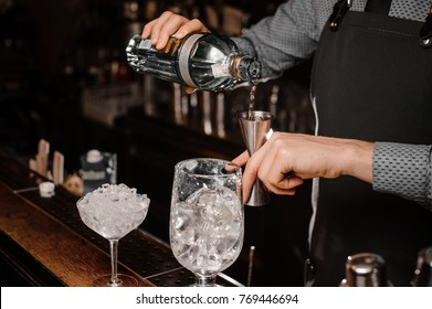 Barman`s hands pouring alcoholic drink into a jigger to prepare a fresh cocktail on the bar counter