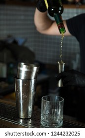 Barmen with black latex gloves pours beverage into jigger from height professionally. Shaker and glass on bar desk.