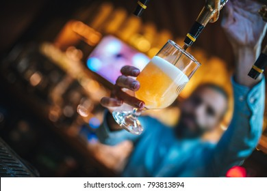Barmen or brewer filling glass with beer. Barmen is pouring lager beer to glass from  beer taps. Bar or night club interior