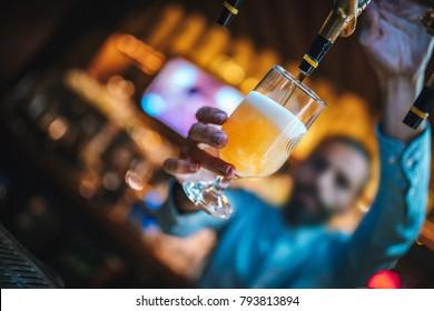 Barmen oder Brauereiglas mit Bier. Barmen gießt Bier aus Bierfässern zu Glas. Inneneinrichtung von Bar und Diskothek