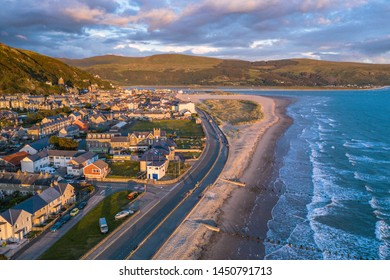 Barmouth laying on estuary of River Mawddach and Cardigan Bay in North-Western Wales. Aerial view in warm stormy sunset light
