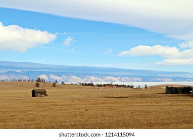 Barn in the middle of golden field not far from a small village in Olkhon island. Blue mountaineous behind iced lake Baikal under white clouds and blue sky