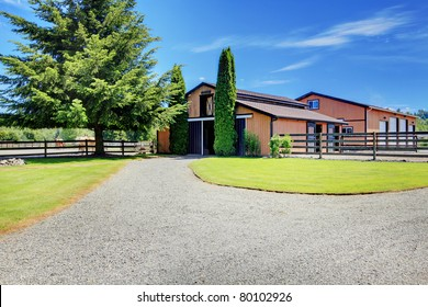 Barn and Pasture ground at the horse ranch in Washington State, USA with the wood fence and the houses in the background.