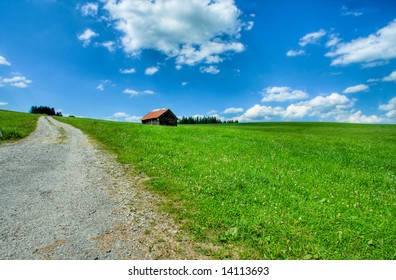 a barn and a path in a green meadow scenery