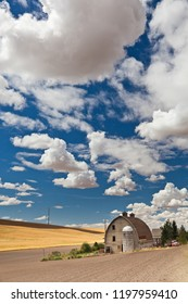 A barn with a silo in the Palouse region of Pullman, WA with a plowed field