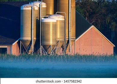 Barn with silos in misty countryside at sunrise.