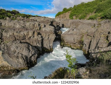 Barnafossar: series of rapids on the Hvítá River, next to Hraunfossar with mountains, azur Hvita River, green forest vegetation and blue sky with clouds in Borgarfjordur region, West Iceland, Europe
