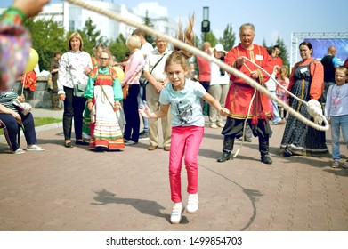 Barnaul, RUSSIA - 24 August 2019: Girl teenager jumps on a large rope. City summer holiday.