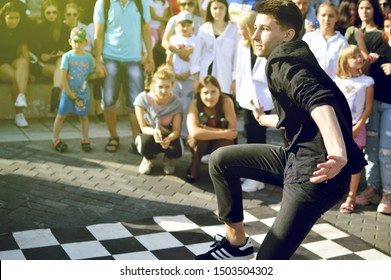 Barnaul, RUSSIA - 24 August 2019: A guy 16 - 20 years old dancing in front of the audience at the dance battle. Summer dance festival.