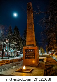 """Barnaul / Russia - Feb 2019: The old Soviet monument with open fire in Barnaul. Cold russian winter in Siberia. Translation is """"From fighting to fallen in fights for Socialism""""."""
