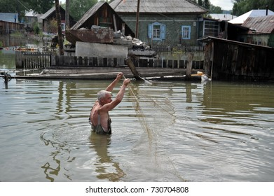 BARNAUL, RUSSIA - JUNE 26, 2010: A local man is fishing with a net during a flood in the garden. The river Ob, which emerged from the shores, flooded the outskirts of the city.