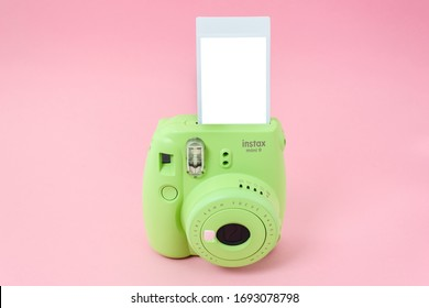 Barnaul, Russia - March 29, 2020: Green instant camera and ready-made photos on pink background. Fujifilm instax mini 9.