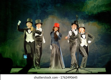 Barnaul, Russia-October 22, 2017. Young actors in tuxedos and hats and singing on the stage of the theater during a theater party