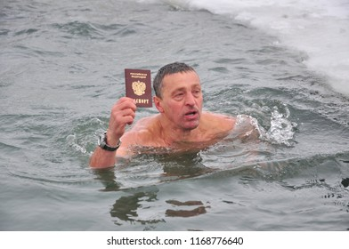 Barnaul,Russia - December 4, 2011.fans of hardening bathe in ice water with the Russian passports in hands