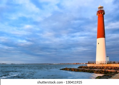 Barnegat lighthouse maritime navigation aid landmark tower in a scenic seashore seascape on the Atlantic coast of the New Jersey shore in sunset light