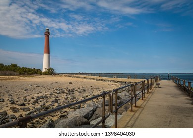 Barnegat Lighthouse on Long Beach Island, NJ, on a sunny spring day with blue sky dotted with clouds