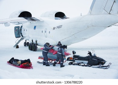 Barneo drifting camp, North Pole - April 10, 2015: Airplane stands on ice. Workers in warm uniform loading luggage snowmobile. Snow on arctic ice.