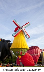 BARNEVELD, THE NETHERLANDS - 17 AUGUST: Colorful windmill and red air balloons taking off at international balloon festival Ballonfiesta in Barneveld on August 17, 2012 in Barneveld, The Netherlands