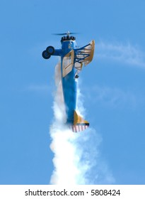 A barnstorming Stearman biplane flying vertically