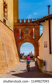 BAROLO, CUNEO, PIEDMONT, ITALY - June 9, 2018: View of the climb to the Castello Comunale di Barolo with cyclist. The area called Langhe is a World Heritage Site.